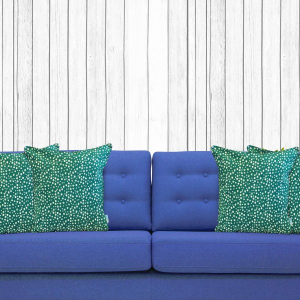 green and white spotted cushion on blue couch
