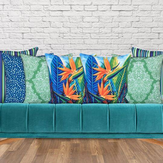 Green designer cushion on blue couch
